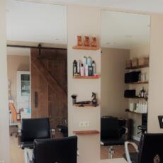 Grote spiegels aan de muur in een kapsalon